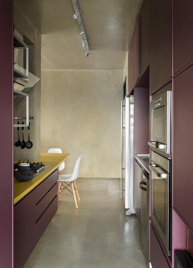 A cozinha apresenta atmosfera vibrante graças às tonalidades escolhidas: vinho para os armários executados pela Florense e amarelo para a bancada com cooktop que se prolonga e forma a mesa de jantar. O Loft Vila Leopoldina tem projeto de reforma assinado pelo arquiteto Diego Revollo