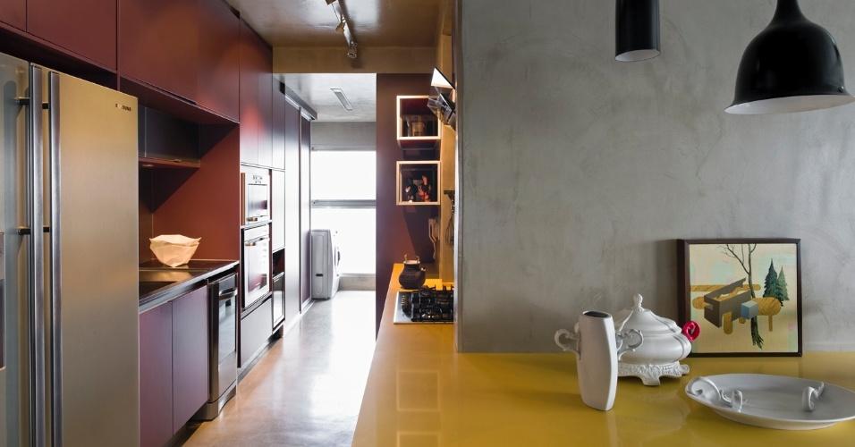 Desenhada pelo arquiteto Diego Revollo, que também assina o projeto de reforma do Loft Vila Leopoldina, a mesa de jantar é estruturada por uma superfície de quartzo amarela. O móvel se prolonga formando uma prática bancada para a cozinha. Os armários planejados, na cor vinho, foram executados pela Florense e embutem os eletrodomésticos