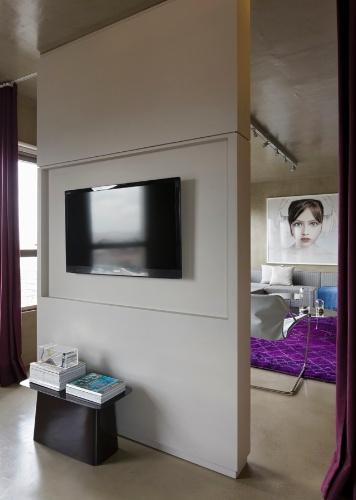 O painel que faz a divisão dos ambientes sustenta TVs em ambos os lados. Nas laterais, as cortinas fecham e dão privacidade aos espaços (quarto e sala). O projeto de reforma do Loft Vila Leopoldina leva a assinatura do arquiteto Diego Revollo