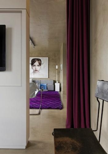 Para delimitar o espaço entre o quarto e o living, o arquiteto Diego Revollo, responsável pelo projeto de reforma do Loft Vila Leopoldina, criou uma solução original: instalou um painel ladeado por cortinas de linhão, da Regatta, no tom vinho escuro, dando um ar teatral ao conjunto