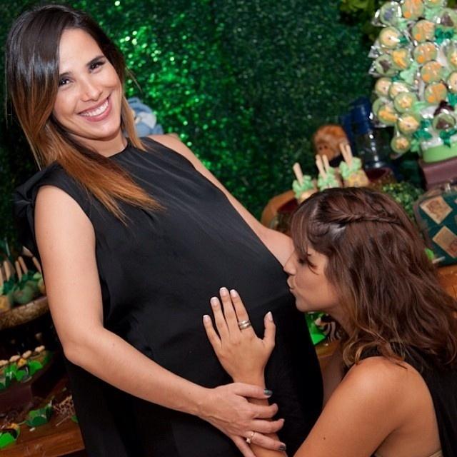 24.mai.2014 - Camila Camargo beija a barriga da irmã, Wanessa, durante chá de bebê do segundo filho da cantora, João Francisco