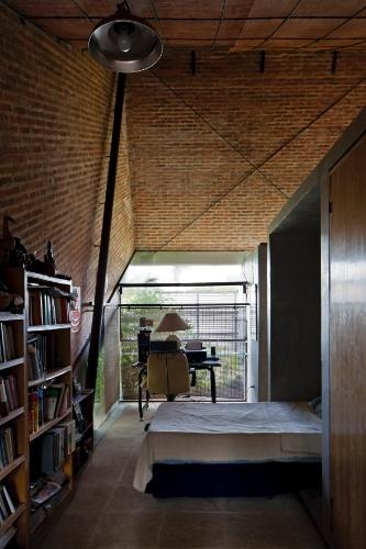 Do lado oposto à cozinha, o módulo multifuncional que subdivide espaços internos da casa Hamaca tem nicho - em alvenaria simples - para acomodar a cabeceira da cama. O corredor entre o quarto e a sala acomoda estantes com livros do escritor, que é sogro do arquiteto projetista da residência, Javier Corvalán. De frente para os livros, um guarda-roupa. Em alvenaria, o móvel é um dos nichos que compõem o módulo central. Ao fundo, voltado para o jardim, o escritório
