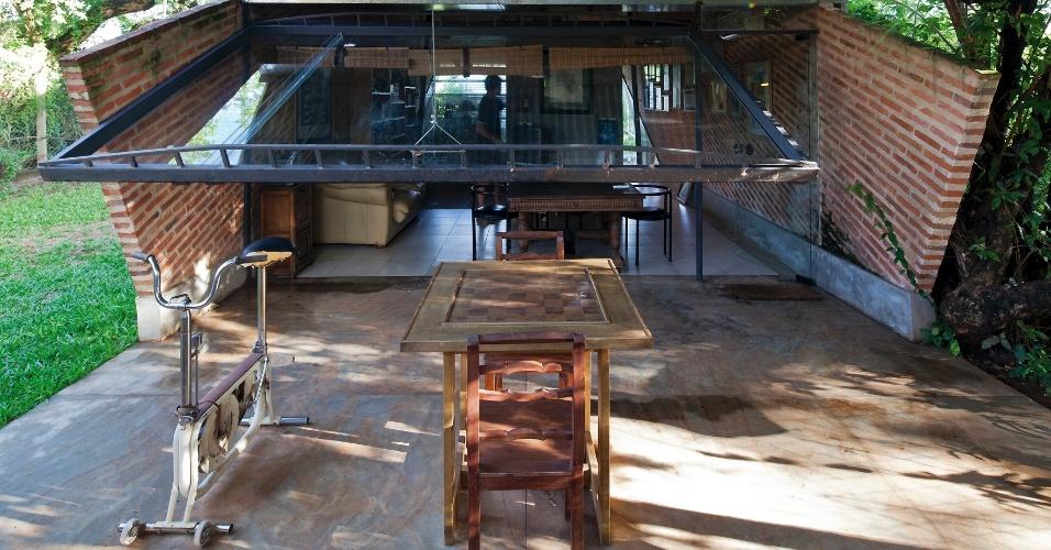 Para reforçar a proteção da varanda em dias de chuva, uma semicobertura de vidro pende, em inclinação, no mesmo ângulo das paredes, impedindo a entrada de água na Casa Hamaca, projetada pelo arquiteto Javier Corvalán