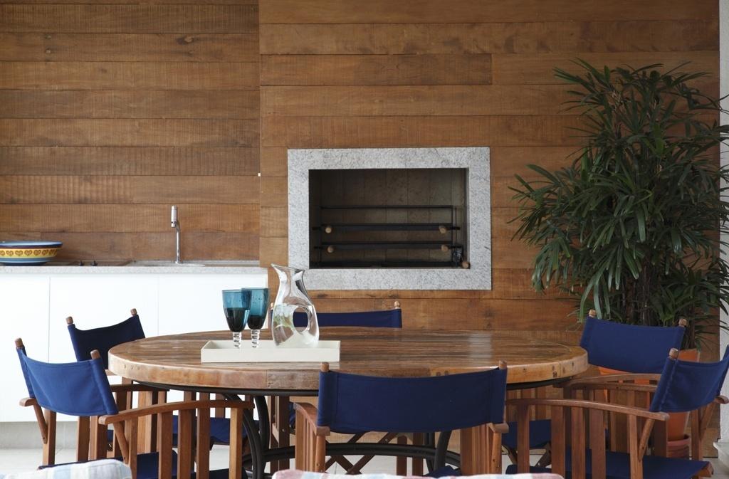 Na proposta do escritório de arquitetura e interiores Messa Penna, o estilo rústico é marcado pela madeira em evidência. O granito da moldura da churrasqueira e o azul das cadeiras (Casual) são fôlego à decoração