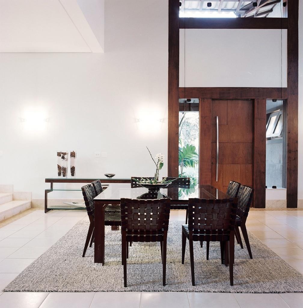 Nesta proposta assinada pela arquiteta Cristina Menezes, a porta executada em carpintaria alia-se com elegância aos móveis  de madeira e linhas retas e aos assentos trançados em couro. O resultado é um ambiente rústico-chique