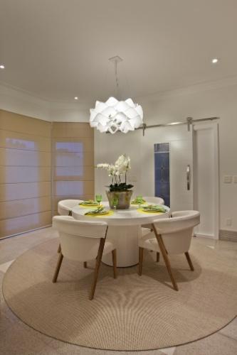 Na sala de almoço da casa do jogador Oscar, em Americana (SP), sobre a mesa de laca branca há um lustre de formas orgânicas. O projeto de arquitetura é de Aquiles Kílaris e o design de interiores tem a assinatura de Iara Kílaris