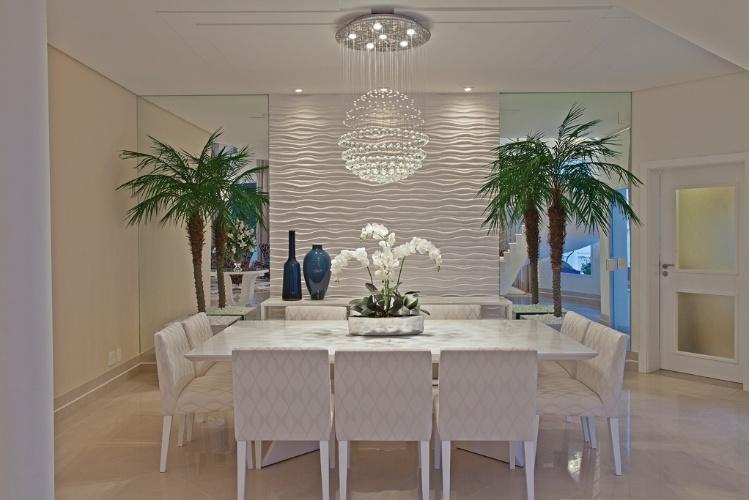 Na sala de jantar da casa do jogador de futebol da seleção brasileira Oscar, em Americana (SP), o lustre de cristal esférico foi combinado à ambientação em tons claros e neutros, na qual chama atenção a parede com textura ondulada e ladeada por espelhos. O projeto de arquitetura é de Aquiles Kílaris e o design de interiores tem a assinatura de Iara Kílaris