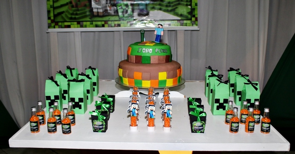 Nessa festa assinada pela Oficina da Kika, a mesa do bolo foi decorada com diversas itens personalizados com o o tema do game Minecraft. Assim como no jogo, as cores verde e preto predominaram na festa