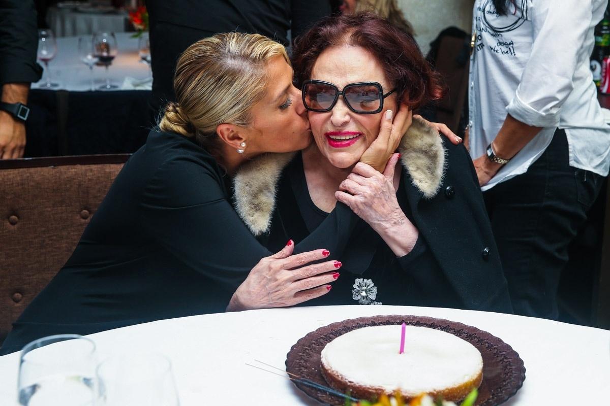1.jun.2014 - Adriane Galisteu dá beijo no rosto de Bibi Ferreira ao comemorar os 92 anos da atriz em um restaurante em São Paulo