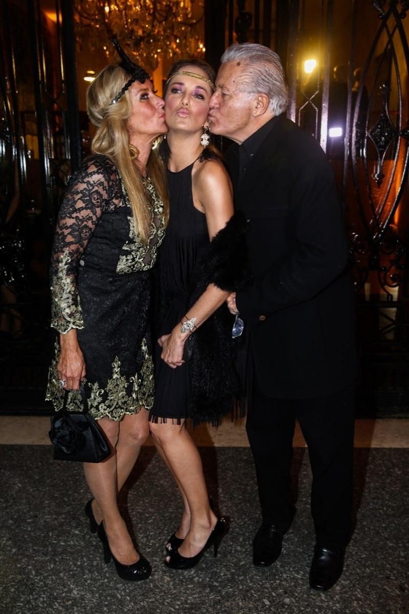 5.jun.2014 - Helô e seu marido, Fernando Pinheiro, dão beijo na filha Ticiane Pinheiro na festa de aniversário de Andrea Guimarães, em São Paulo. A festa teve como tema