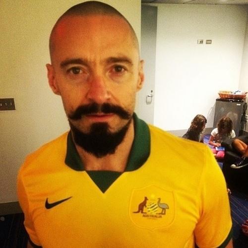 """11.jun.2014 - Hugh Jackman vestiu a camisa da Austrália para torcer por seu país de origem na Copa. De cabelo raspado e barba para o seu personagem no filme """"Pan"""", o ator falou: """"Vamos lá, Austrália!"""". O primeiro jogo da Austrália será contra a Espanha, na sexta"""