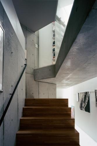 A escadaria que vai da galeria de entrada ao primeiro pavimento revela uma arquitetura de lajes de concreto espessas e cartesianamente recortadas, com detalhes de paredes e forros que expõe o material estrutural, em sua forma lixada. A escada recebe palitos de eucalipto tratado, para contrastar com a temperatura fria do concreto e enriquecer o aspecto rústico e natural dos interiores. A Casa TN fica em Tóquio, no Japão, e foi projetada por Tsuyoshi Ando