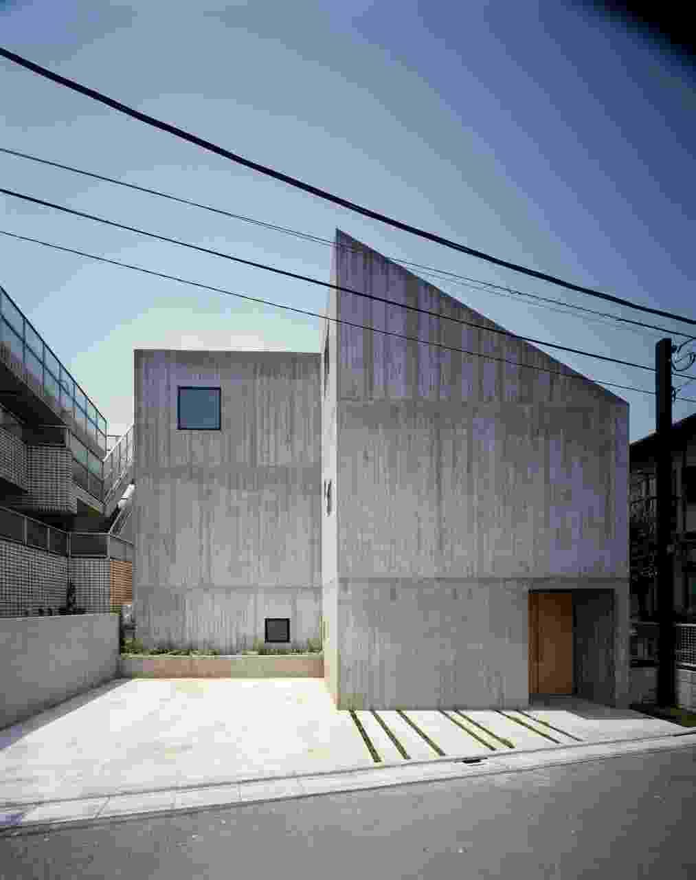 A fachada da Casa TN, do arquiteto japonês Tsuyoshi Ando, mantém uma linguagem sóbria, geométrica e que preza pela privacidade de seus moradores. A entrada de luz natural não se dá pelas janelas voltadas para a rua, mas por claraboias na cobertura e através de vãos envidraçados junto ao pátio interno (quintal). Da rua, o que se vê são paredes de concreto aparente e uma garagem para dois carros - Kai Nakamura/ Divulgação