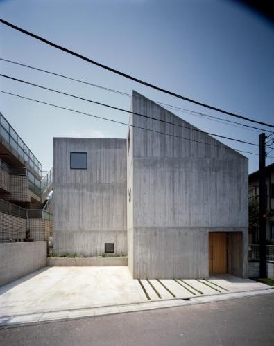A fachada da Casa TN, do arquiteto japonês Tsuyoshi Ando, mantém uma linguagem sóbria, geométrica e que preza pela privacidade de seus moradores. A entrada de luz natural não se dá pelas janelas voltadas para a rua, mas por claraboias na cobertura e através de vãos envidraçados junto ao pátio interno (quintal). Da rua, o que se vê são paredes de concreto aparente e uma garagem para dois carros