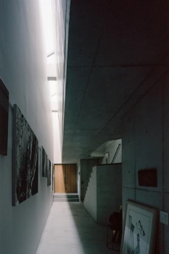 A luz natural que ilumina as gravuras da moradora da Casa TN, em Tóquio, entra por uma extensa claraboia em caixilhos de alumínio. A parede-empena que recebe as gravuras em exibição foi executada em painéis de gesso acartonado. Há espuma de poliuretano (isolante térmico) entre os painéis e a parede externa de fachada, que é de concreto aparente. Projeto do arquiteto japonês Tsuyoshi Ando