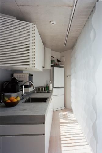 As persianas Silent Gliss (à dir.), de uma fabricante japonesa, são fabricadas sob encomenda e podem ser automatizadas ou operadas manualmente. O equipamento destaca-se por seu design ondulado e protege a cozinha do andar térreo da Casa TN da incidência direta do sol, cobrindo portas de correr de vidro voltadas para um lance de escadas para o jardim, em nível mais elevado que o próprio piso da convivência interna.  A arquitetura é de Tsuyoshi Ando