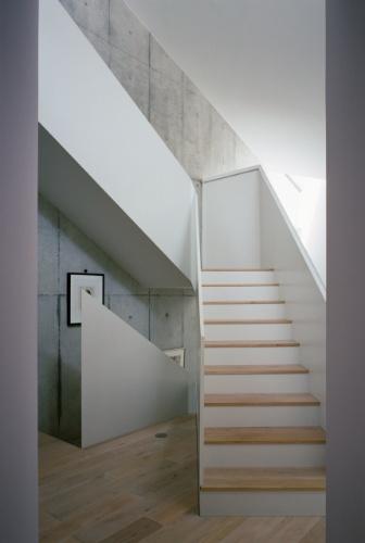 Escada de circulação entre pavimentos da Casa TN. Seus degraus, assim, como o piso, são revestidos por eucalipto, madeira que aquece os interiores, principalmente onde paredes estruturais exibem o concreto rústico, moldado com fôrmas de madeira. O projeto é de Tsuyoshi Ando
