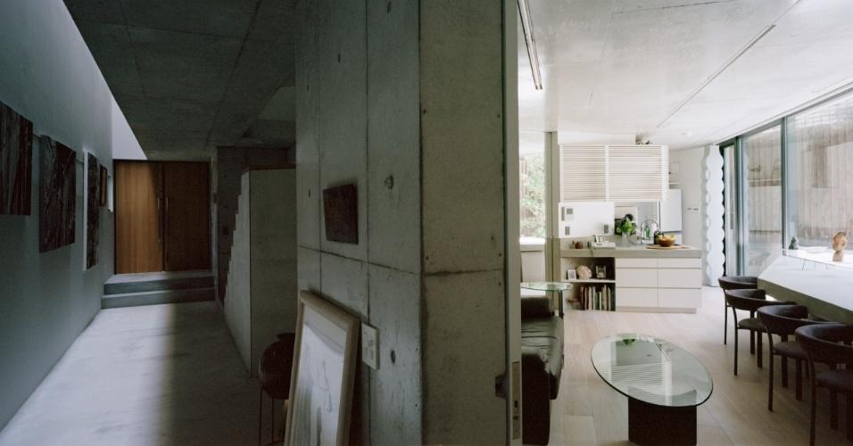 No andar térreo, de um lado, estão expostas as gravuras da matrona residente na Casa TN, do outro, separada por espessa parede estrutural de concreto armado modulado em fôrmas, fica a área social da morada desta senhora com cozinha integrada às salas de jantar e estar. Dos dois lados, o forro expõe irregularidades e a textura do concreto lixado e resinado. Arquitetura é de Tsuyoshi Ando