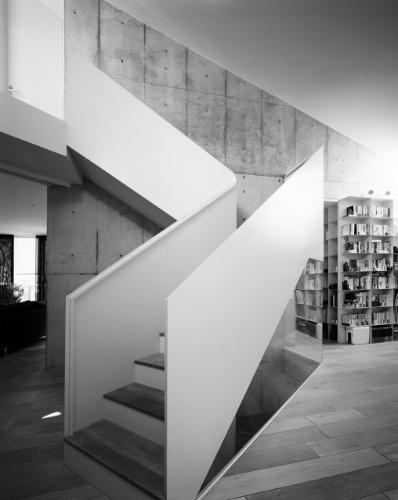 No primeiro andar, o hall de escadas para circulação entre os três pavimentos da Casa TN dá acesso a duas entradas para a segunda área social integrada da residência, de uso exclusivo do casal. À esquerda, está o living, e pela direita, através de um corredor com estantes para livros, chega-se à cozinha