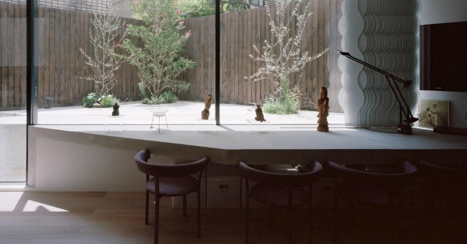 O quintal é cercado e protegido por um muro de tábuas de madeira tratada e o paisagismo está inserido em recortes feitos no piso cimentado. Do quintal, também fica explícito o desnível em relação ao piso térreo (enterrado): na verdade, é a mesa de jantar (fixa, em concreto armado) que está na mesma cota do jardim. A arquitetura é de Tsuyoshi Ando