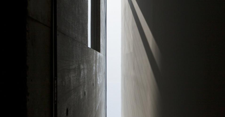 Paredes paralelas que formam o corredor de entrada à Casa TN, do arquiteto japonês Tsuyoshi Ando, aproximam-se à medida que alcançam a altura máxima do pé direito, de quase seis metros. Do lado da empena, paredes são de painéis de gesso acartonado. A outra parede é de concreto estrutural aparente e modular, executada em fôrmas de madeira. Ambas não chegam a tocar os limites da altura máxima, que termina numa claraboia de caixilhos de alumínio