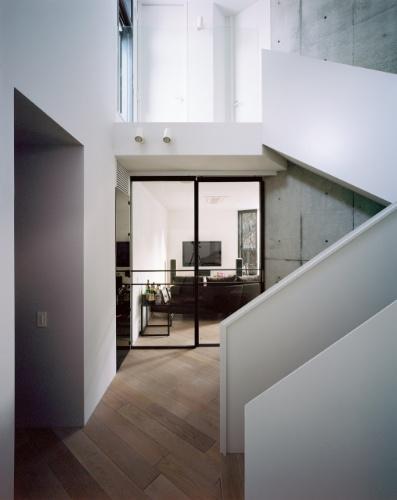 Uma porta de vidro encaixilhada em alumínio separa o hall do living integrado, no primeiro andar. A Casa TN fica em Tóquio, no Japão