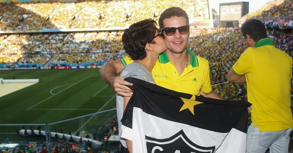 12.jun.2014 - Sophie Charlotte dá beijo no rosto de Daniel Oliveira enquanto ele segura uma bandeira do time Atlético Mineiro em camarote na Arena Corinthians, em São Paulo, durante a abertura da Copa do Mundo