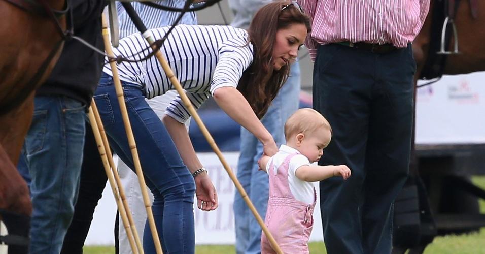 15.jun.2014 - Príncipe George anda com o auxílio da mãe, a Duquesa Kate Middleton, durante partida de polo beneficente na Inglaterra