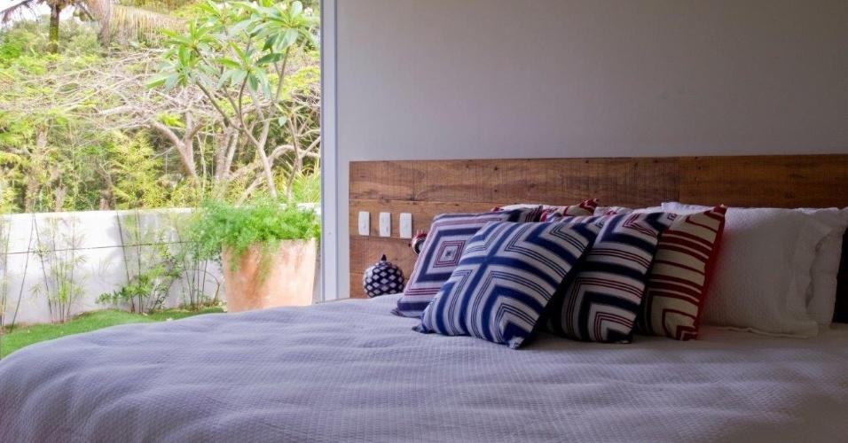 Com uma decoração mais despojada, os quartos de hóspedes (como o da foto), que ficam no térreo, têm cabeceiras em madeira de demolição e cores pautadas no azul marinho e vermelho. O projeto de interiores da casa de praia é assinado por Marília Veiga