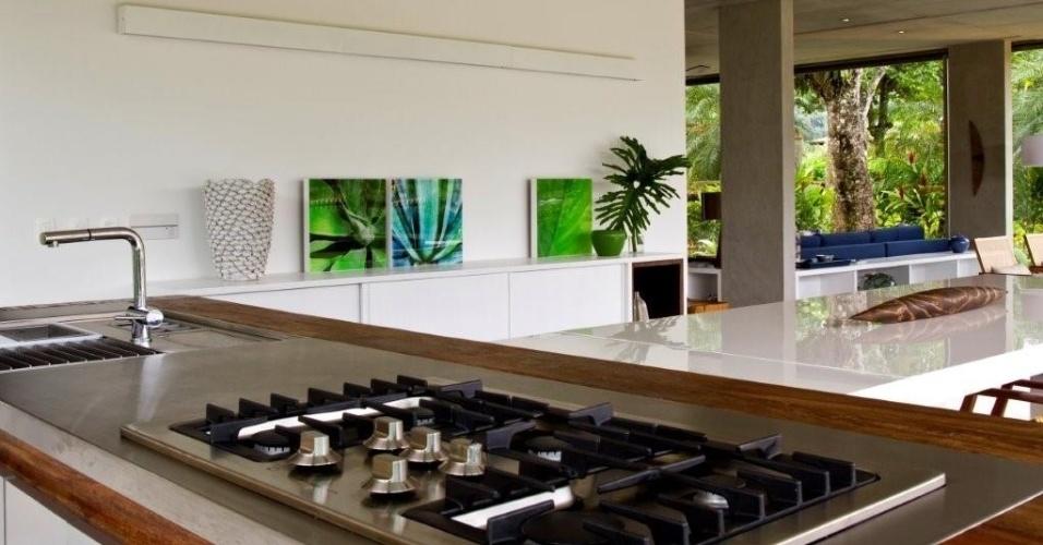 No espaço gourmet, para que o cozinheiro pudesse preparar as refeições e ao mesmo tempo conversar com seus convidados, a decoradora Marília Veiga posicionou a bancada em aço inox, com pia e cooktop, junto à mesa de jantar (Clami) em laca branca