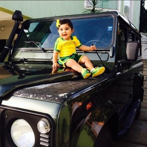 """17.jun.2014 - César Menotti se diverte com a filha Júlia em cima do carro. """"Juju no clima da Copa"""", disse o sertanejo sobre o look verde e amarelo da herdeira"""