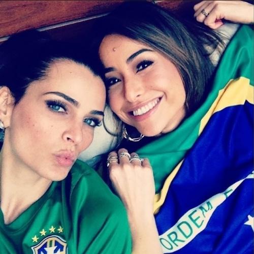 17.jun.2014 - Fernanda Motta posta foto segurando a bandeira do Brasil com Sabrina Satto em jogo da Seleção contra o México