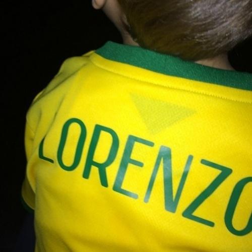 """17.jun.2014 - Luciana Gimenez veste o filho Lorenzo com uma camisa customizada com o nome do menino. """"Cute (fofo)"""", disse a apresentadora da RedeTV!"""