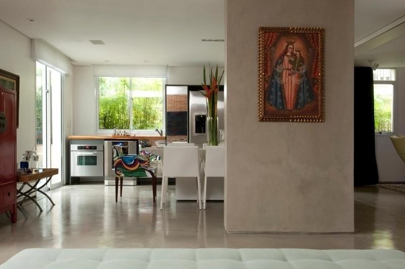 Integrado à cozinha gourmet do apartamento Alto de Pinheiros, em São Paulo, está o living - separado dela apenas por uma coluna estrutural que teve de ser mantida, após a reforma do piso térreo. A coluna é revestida por cimento queimado cinza, neutro e brilhante, assim como o piso. O projeto é dos arquitetos Gabriel Magalhães e Luiz Cláudio Souza