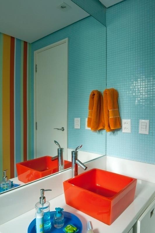No banheiro das crianças, uma das paredes foi pintada com listras em tons de azul, amarelo e laranja. Uma cuba de resina laranja apoia-se na bancada composta por pó de mármore e vidro. As louças são da Deca, e os metais, Lorenzetti. O projeto de reforma do apartamento Alto de Pinheiros, em São Paulo, é dos arquitetos Gabriel Magalhães e Luiz Cláudio Souza