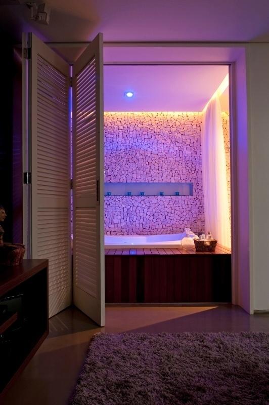 No home theater do apartamento Alto de Pinheiros, o tapete cinza felpudo (Avanti), além de aquecer o ambiente, tem papel de