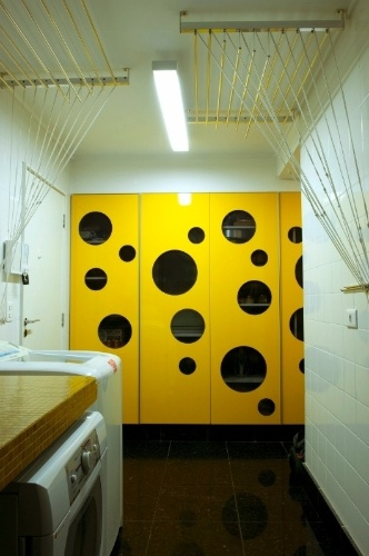 O amarelo foi a cor escolhida para a área de serviços e está no armário com portas vazadas. As paredes levam azulejos brancos 15 cm x 15 cm e a bancada foi executada em concreto e revestida por pastilhas de vidro (à esq.). O piso é o mesmo da cozinha e foi instalado pela construtora, antes da reforma: granito preto São Grabriel
