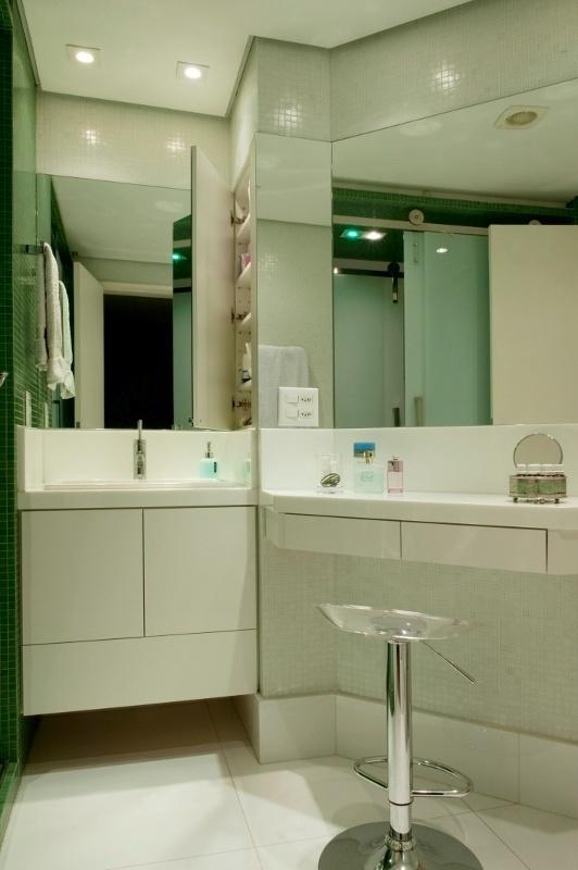 O lado feminino do banheiro da suíte máster tem bancada para maquiagem, com longo armário espelhado e assento. O apartamento Alto de Pinheiros fica em São Paulo e teve reforma projetada pelos arquitetos Gabriel Magalhães e Luiz Cláudio Souza