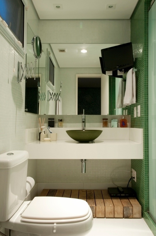 O lado masculino do banheiro da suíte máster também tem bancada, piso e rodapés em composto de vidro e pó de mármore.  O vaso sanitário, assim como metais, são Deca, e, na parede, as pastilhas de vidro Colormix acompanham o mesmo revestimento do box compartilhado com a esposa
