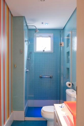 O banheiro das crianças tem piso e paredes revestidos por pastilhas de vidro azuis da Colormix. Para aumentar a diversão, foram pintadas listras em uma das paredes