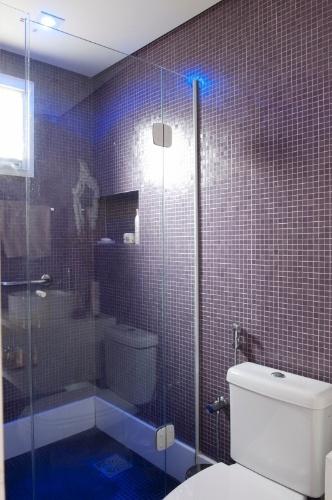O banheiro de hóspedes do apartamento Alto de Pinheiros foi inteiramente revestido por pastilhas de vidro em tons de roxo e lilás. A reforma da residência é um projeto dos arquitetos Gabriel Magalhães e Luiz Cláudio Souza