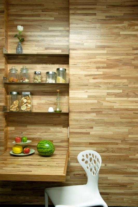 Painéis de madeira que revestem e aquecem paredes da cozinha e a mesa dobrável para pequenas refeições são executadas em madeira teca. A ideia foi dos arquitetos Gabriel Magalhães e Luiz Cláudio Souza, responsáveis pela reforma do apartamento Alto de Pinheiros, em São Paulo