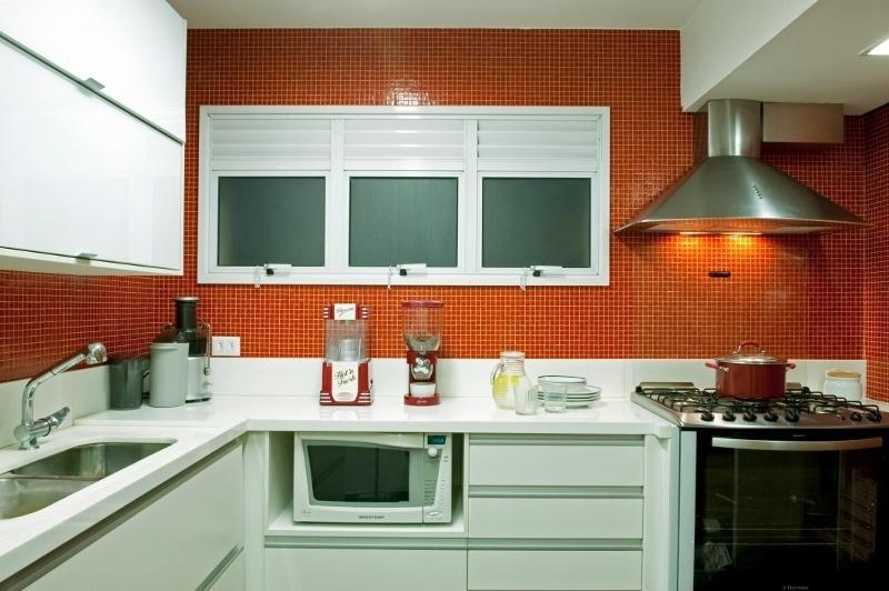 Tampo de composto de pó de mármore e vidro e armários de MDF com portas de vidro branco (Florense) colaboraram, junto das pastilhas laranja de vidro (Colormix), para