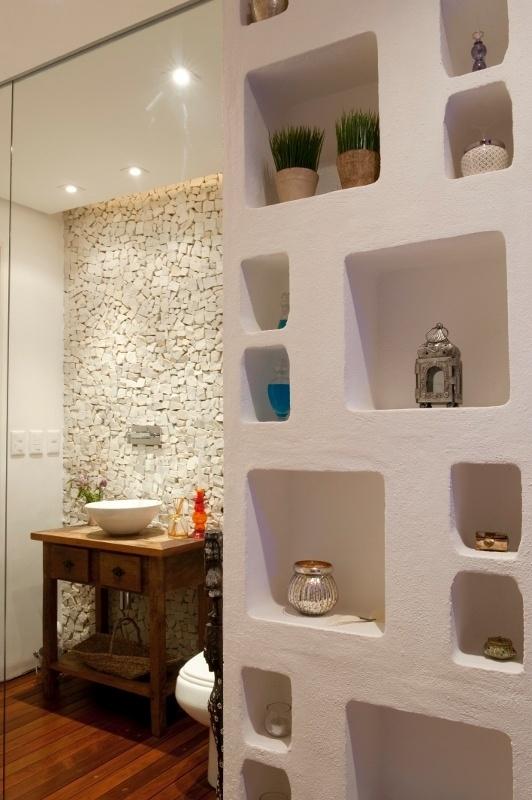 Uma estante moldada com concreto (Solim) oferece nichos de três tamanhos combinados e sobrepostos, como em um jogo de montar. O móvel guarda sais de banho no
