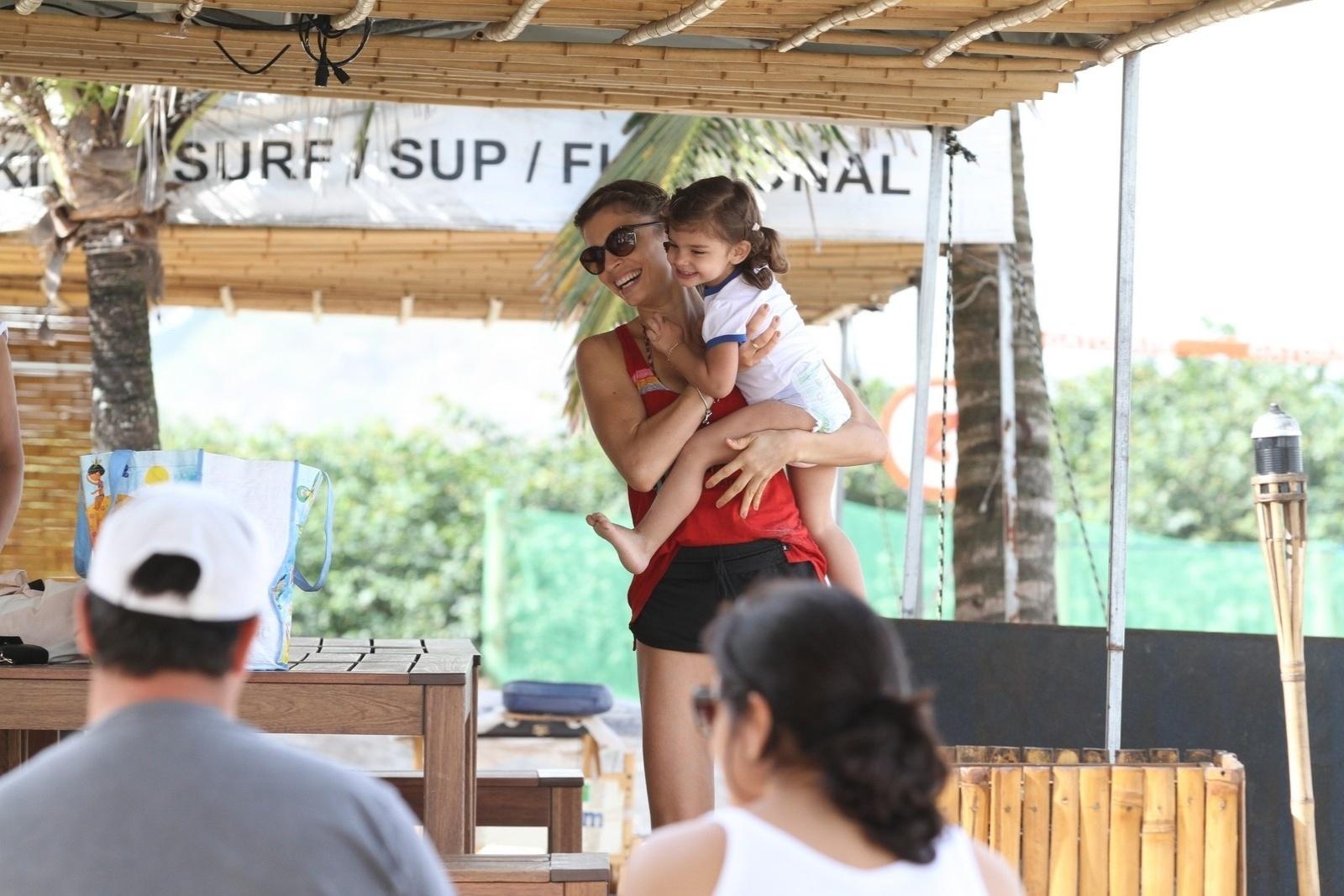 23.jun.2014 - Grazi Massafera brinca na praia da Barra da Tijuca, Zona Oeste do Rio, com a filha Sofia. Após se divertirem na areia, as duas aproveitaram para beber água de coco em um quiosque. Elas estavam acompanhadas da atriz Ana Lima, que fez caminhada com Grazi
