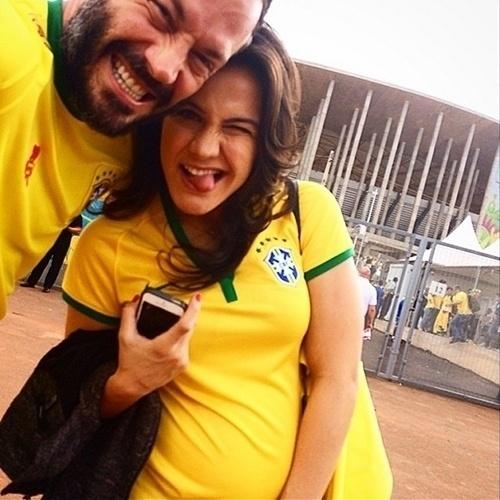 """23.jun.2014 - Malvino Salvador e Kyra Gracie vão ao estádio Mané Garrincha, em Brasília, para acompanhar a partida entre Brasil e Camarões. Grávida de uma menina, a primeira filha do casal, a lutadora exibiu a barriguinha em uma camisa da Seleção. """"Estamos chegando!!!! #vaibrasil #brasilxcamarões"""""""