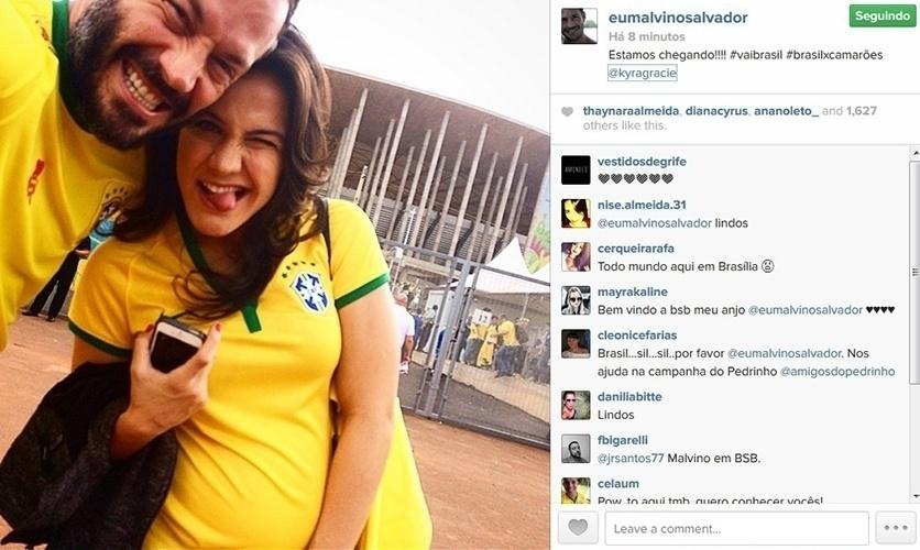 23.jun.2014 - Malvino Salvador e Kyra Gracie vão ao estádio Mané Garrincha, em Brasília, para acompanhar a partida entre Brasil e Camarões. Grávida de uma menina, a primeira filha do casal, a lutadora exibiu a barriguinha em uma camisa da Seleção.