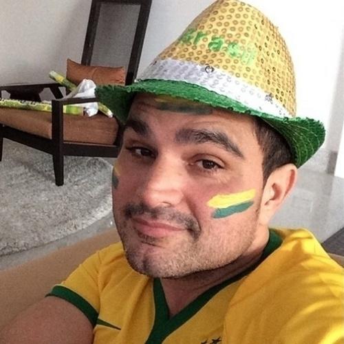 23.jun.2014 - O cantor Luciano, da dupla com Zezé Di Camargo, pinta o rosto e coloca chapéu e camisa com as cores do Brasil para torcer pela Seleção, que joga contra Camarões nesta segunda-feira, em Brasília.