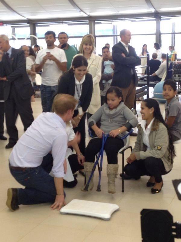 23.jun.2014 - Príncipe Harry se ajoelha e conversa com crianças do hospital e centro de reabilitação Sarah, no Lago norte, em Brasília