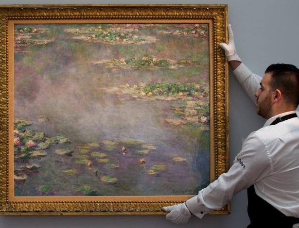 """Funcionário da Sotherby segura quadro da série """"Nenúfares"""", de Claude Monet, vendido por US$ 54 milhões - Andrew Cowie/AFP Photo"""